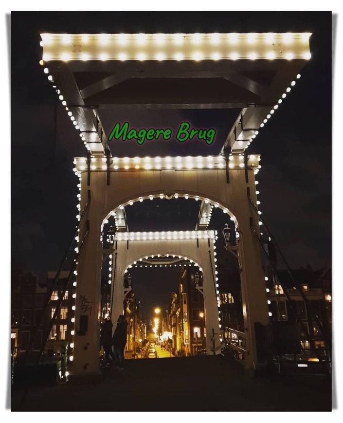 Magerebrug in de avond. Lampu-lampu Amsterdam. Jembatan Kayu Magere Brus, Skinny Bridge, Wisata Jalur Utara, Belanda, Serbalanda Tour
